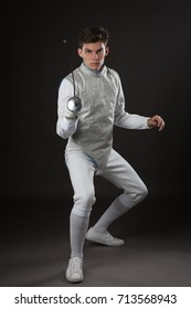 Portrait of Young male fencer in white fencing costume. Attacking pose against dark Background