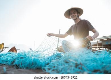 Portrait of a young male fisherman preparing a fishing net