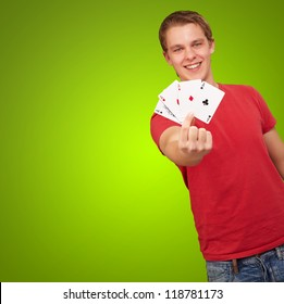 portrait of a young male holding four aces on green background