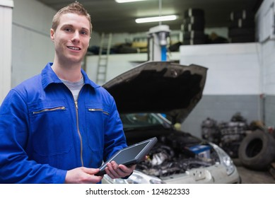 Portrait of young male mechanic with digital tablet at garage