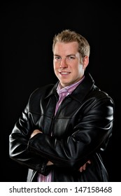 Portrait of a young male model wearing a black leather jacket and colorful striped shirt.  He's smiling with his arms crossed and is shot on a black background.