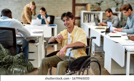 Portrait of young male office worker in a wheelchair smiling at camera while posing in co-working space. Colleagues in the background. Disability and handicap concept. Horizontal shot. Selective focus