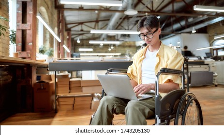 Portrait of young male office worker in a wheelchair looking at the screen of his laptop while performing in co-working space. Disability and handicap concept. Horizontal shot. Selective focus