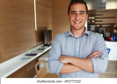 Portrait of young male office worker.He standing in office and looking at camera.