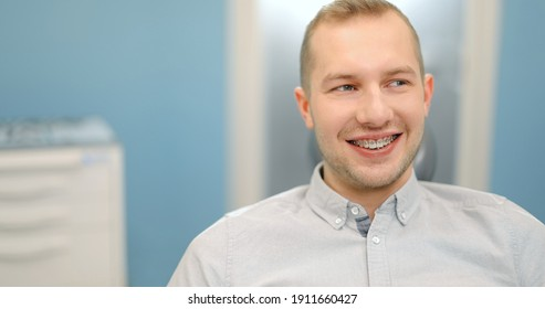 Portrait of a young male patient wearing dental braces smiling at camera, sitting on a dental chair during an orthodontic visit. 4k video screenshot, please use in small size
