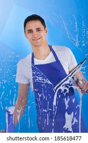 Portrait of young male servant cleaning glass with squeegee over blue background