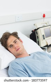 Portrait of young male sick man lying in hospital bed
