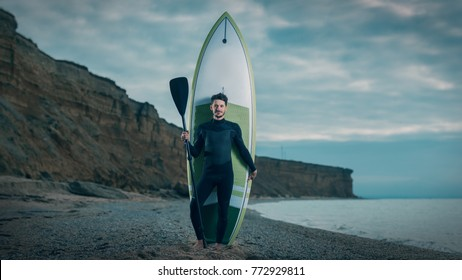 Portrait of a young male surfer in a wetsuit on the beach.