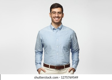 Portrait of young male teacher in blue shirt isolated on gray background