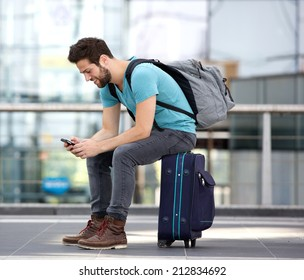Portrait of a young male traveler sitting on suitcase and sending text message