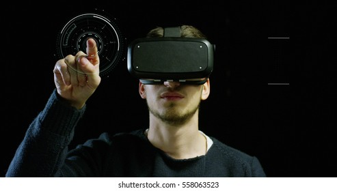 Portrait of young man with 3D virtual reality glasses enjoys his trip in an adventurous world on a dark background. Concept of connection technology with science, augmented future, global web
