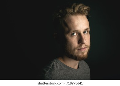 portrait of young man above black background