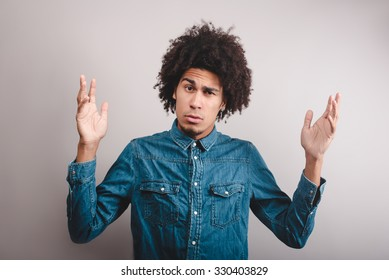 Portrait of a young man with afro asking questions with hands raised