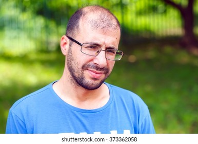 portrait of young man with bad eyesight and hair loss.