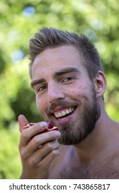 Portrait of a young man with a beard eating a pomegranate in the nature on a summer day, close up
