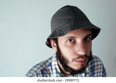 Portrait of young man with beard and hat.