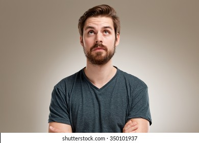 Portrait of young man with beard, looking up verry straight