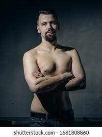 Retrato de un joven con barba y torso desnudo sobre un fondo oscuro