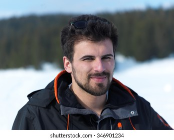 portrait of young man with beard and sunglasses on fresh snow at beautiful sunny winter day with forest in background