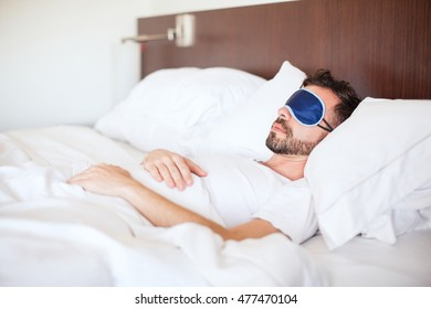 Portrait of a young man with a beard using a sleep mask to get some rest in a hotel