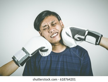 portrait of a young man being smacked in the face in a fist fight.,Asian Men in boxing gloves are smashing faces.,Asian man is getting punch in face with fist.,conflict concept