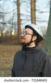 Portrait of a young man in biker helmet with closed eyes and a contented smile enjoys warm sun on a blurred background of a city Park. Side view, closeup.
