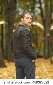 Portrait of young man in black jacket in autumn park, looked over his shoulder, view from back