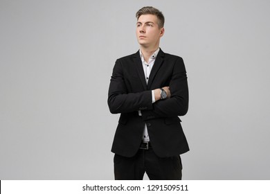 Portrait of young man in black suit with arms crossed isolated on white background