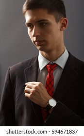 Portrait of young man in black suit keeping his hand with wristwatch on his chest