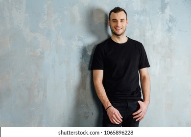 portrait of a young man in a black T-shirt leaned against a vintage gray wall. Copy space. Masculine model of bristles. Happy smiling.