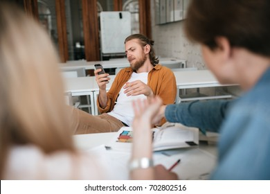 Portrait of young man with blond hair and beard sitting throw his legs on table and using cellphone in classroom. Boy with mobile phone in hands and book on table ignoring his friends