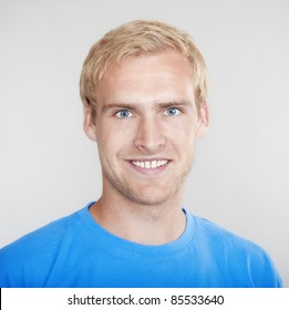 portrait of a young man with blond hair smiling - isolated on light gray
