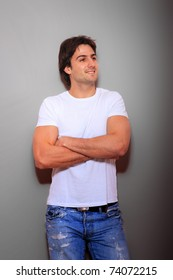 portrait of a young man blue jeans and white tshirt  over light gray wall