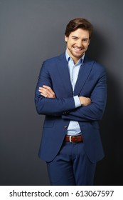 Portrait of young man in blue suit standing against black wall background with arms folded, looking at camera and smiling