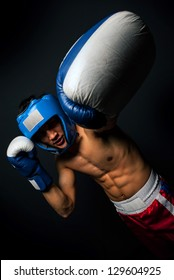 Portrait of young man with boxing helmet and gloves over black background