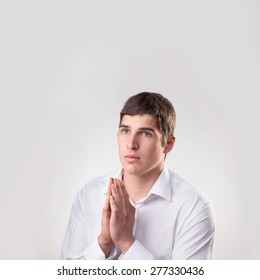 portrait young man bright-eyed blonde  praying isolated on white background standing