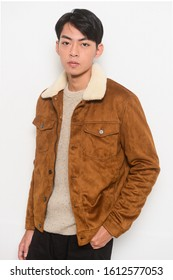 portrait of young man in brown jacket with,black jeans , ,standing on white background