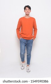 portrait of young man in brown sweater with blue jeans standing on white background