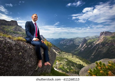 portrait of a young man in a business suit at the top of the mountain on the background of mountains and blue sky on a sunny summer day