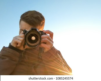 portrait of a young man with a camera. the man is looking at the camera. portrait against a blue sky with sun rays. concept.