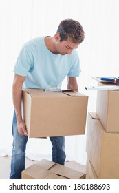 Portrait of a young man with cardboard boxes in new house