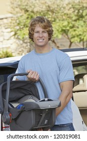 Portrait of a young man carrying baby carrier with car in the background