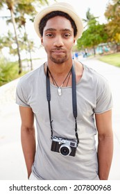 Portrait Of Young Man Carrying Camera