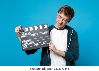 Portrait of young man in casual clothes holding looking on classic black film making clapperboard isolated on blue background in studio. People sincere emotions, lifestyle concept. Mock up copy space