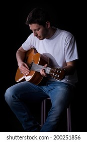 Portrait of a young man in casual clothes playing guitar