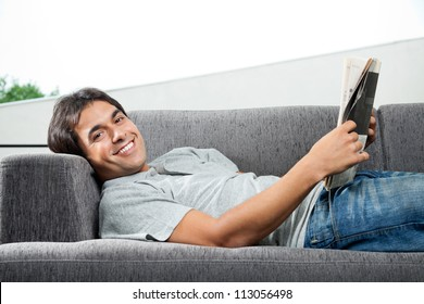 Portrait of young man in casual wear lying on sofa with a magazine
