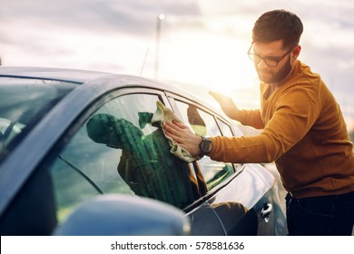 Portrait of a young man cleaning his car with a cloth outdoors at sunset.