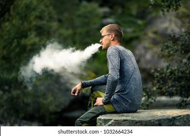 Portrait of young man close up vaping outside, huge smoke on the photo. Green background. Norway.
