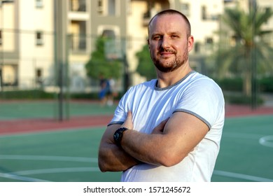 Portrait of young man coach is standing in front of players.Coach stands looking direct at camera while standing with cross hands. Close up of young coach in white t shirt standing on basketball court