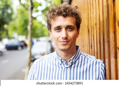portrait of a young man with curly blonde hair looking to camera outside on the street